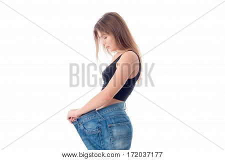 slender girl stands sideways in large wide jeans isolated on white