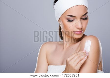 Young woman with white headband putting cream on her shoulder. Looking aside and down. Studio, indoors, head and shoulders, closeup, grey background