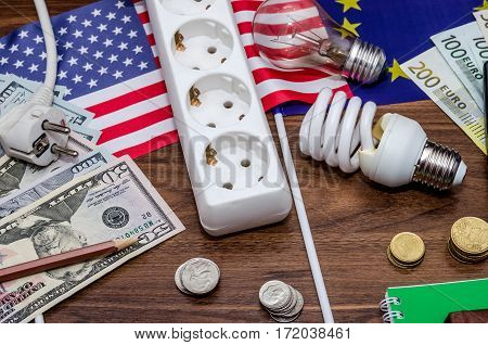 The Concept Of Saving Money. Bulbs With Dollars And Euro Banknotes