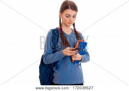 sad smart student girl with backpack on her shoulders and folder for notebooks in her hands looking down isolated on white