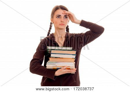 tired smart student girl in brown sport clothes with a lot of books in her hands posing isolated on white