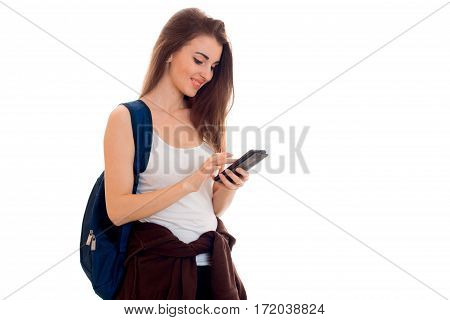 cheerful smart student girl in brown sport clothes with backpack on her shoulders looking at her mobile phone and smiling isolated on white