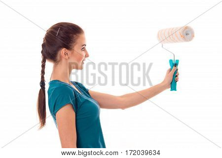 portrait of young cute brunette building woman in uniform with paint roller in hands makes renovation isolated on white