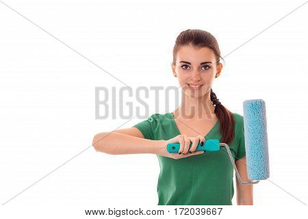 portrait of young lovely brunette building woman in uniform with paint roller in hands makes renovation and smiling on camera isolated on white