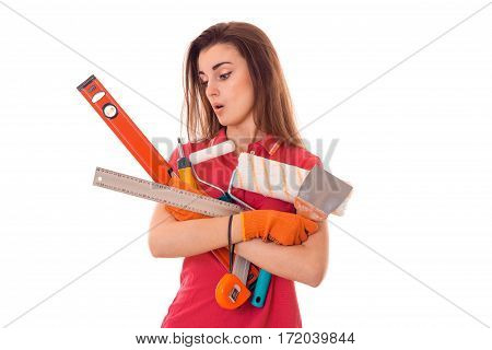 portrait of young surprised brunette building woman in red uniform with tools in hands makes renovation isolated on white