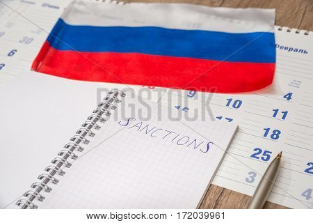 sanctions for russia  - notepad pen and flag