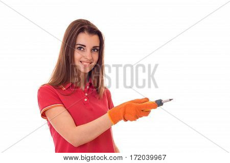 portrait of young attractive brunette building woman in red uniform with screwdriver in hands makes renovation and smiling on camera isolated on white
