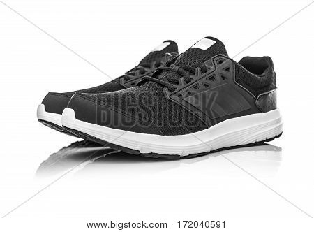 Black unbranded sneakers isolated on white background.