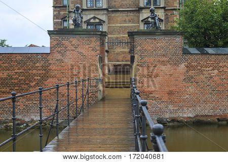 COPENHAGEN, DENMARK - JUNE 29, 2016: This is passage and the bridge across the moat of the castle Rosenborg in the rose garden.