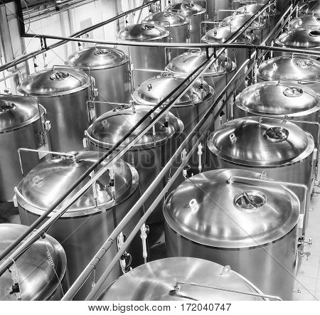 Rows of tanks made of stainless steel in the shop. The food industry, beer production. Poor lighting.