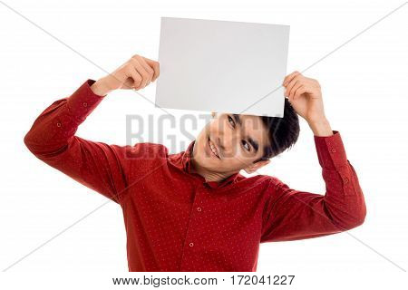 funny young stylish man in red shirt posing with empty placard in his hands and looking up isolated on white