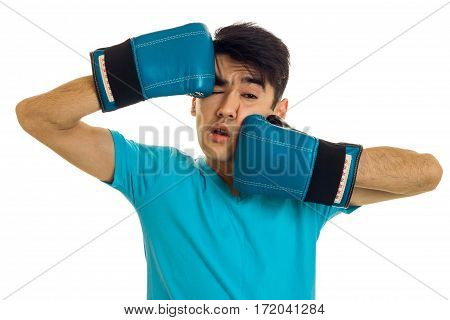 portrait of funny brunette sports man practicing box in blue gloves isolated on white