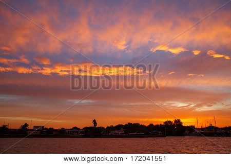 Beautiful amazing sutset view from the water. Colored orange clouds in blue sky.