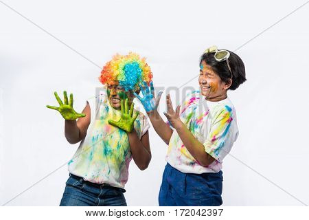 indian siblings playing colours, kids celebrating holi with gulal and pichkari, isolated over white