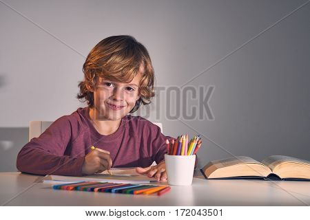 Child drawing with colors in his house