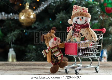 Happy Christmas characters pushing shopping cart.  Christmas tree in background.