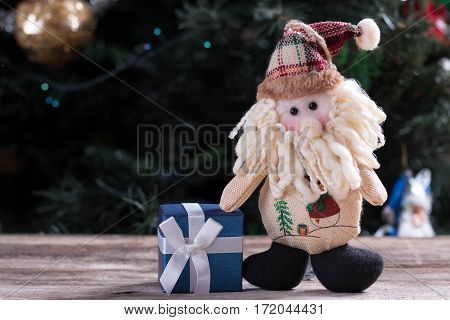 Funny Santa Claus standing near Christmas present