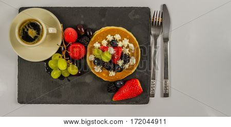 The large pancake with whipped cream and fresh fruit strawberries blueberries blackberries black coffee in a cup black stone plate a delicious dessert