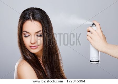 Beauty portrait of young girl with perfect nude make-up, closed eyes. Someone sprinkling hairspray on her loose hair. Beauty salon. Head and shoulders, studio, indoors