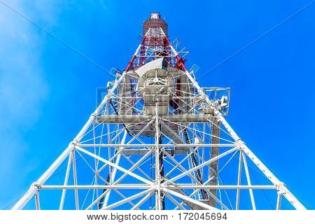 High angle view of communication tower with antenna and satellite dish wave transmitter pylon against blue sky with clouds