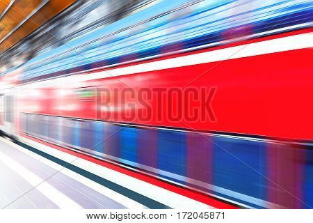 Modern red high speed electric passenger commuter double deck train at station platform with motion blur effect