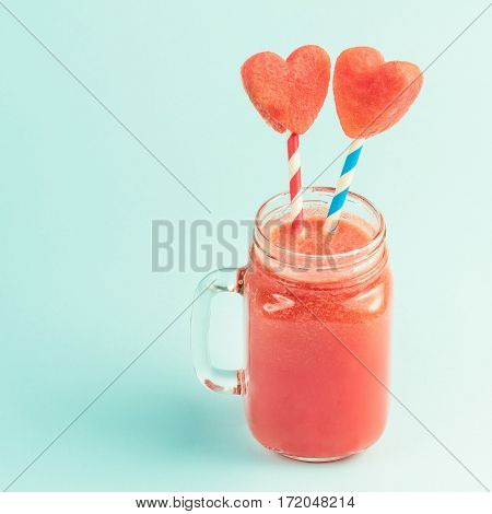 Watermelon smoothie in Mason jar with straws decorated with watermelon slices curved like heart symbols