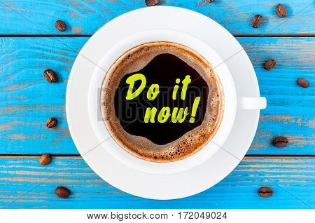 Coffee cup with inspiration text DO IT NOW on blue rustic desk from above, motivational concept.