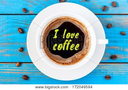 White ceramic cup with I LOVE COFFEE text. Standing on a rustic kitchen table with coffee beans. Top view.