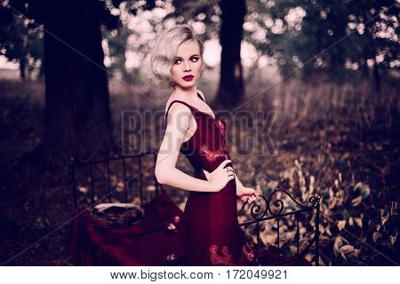 Beautiful And Elegant Blonde Woman With Red Lips And Hair Waves Wearing Wine Red Nightie Posing On T