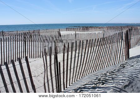 Multiple snow fences at different angles installed on a beach to keep winter erosion to a minimum.