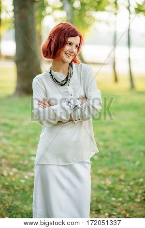 Portrait Of Red Haired Girl Wearing On White Dress Against Park At Hen Party.