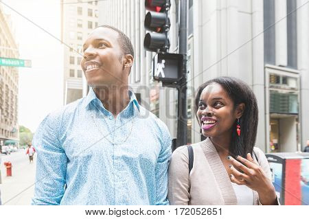Happy black couple walking in Chicago. A man and a woman together in the city looking away from camera with skyscrapers on background. Lifestyle and travel concepts.