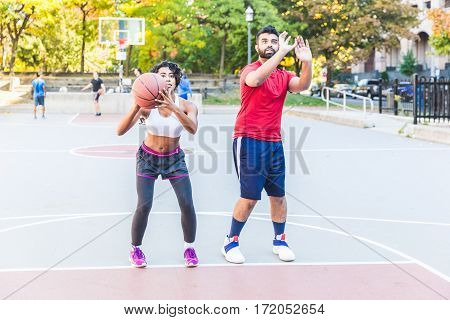 Black man giving basket lesson to a black woman. Instructor and junior athlete on the court during a training session. Sport and teamwork concepts.