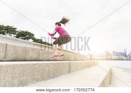 Young Woman Doing Legs Exercises With Chicago Skyline On Background
