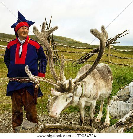 Honningsvag, Norway - April 20, 2017: Reindeer and Laplander deer-breeder in Honningsvag, Norway.