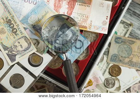 Different Collector's Coins And Banknotes With A Magnifying Glass