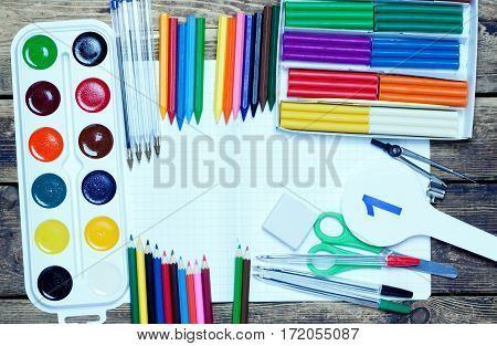 back to school.background.Various school supplies lie on a wooden surface.top view