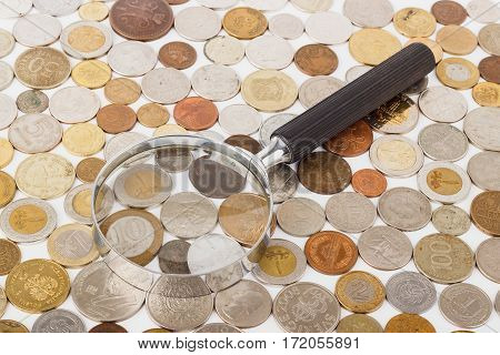 Different Gold And Silver Collector's Coins And Magnifying Glass