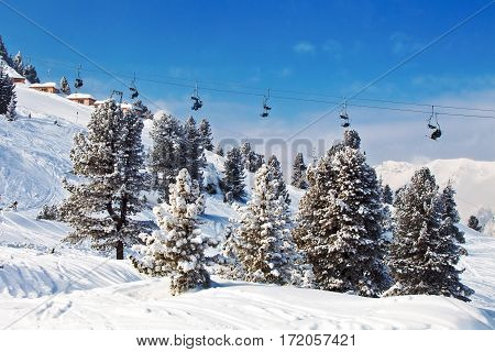Chair ski lifts with skiers over blue sky in Mayrhofen, Austria