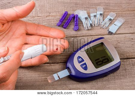 The blood glucose meter with a hand on an old wooden background .