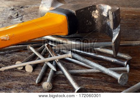 A low angle image of an old used yellow hammer and a pile of nails on a wooden workbench.