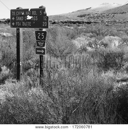 A sign in the brush and bushes of Central Oregon's High Desert vandalized by being used for target practice on a winter day.