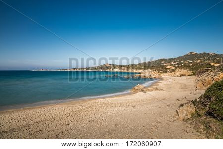 Turqouise Mediterranean sea washing gently onto a deserted golden sandy Arinella beach in the Balagne region of Corsica with the Genoese tower at Punta Daldanu in the distance