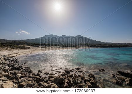 Deserted Bodri beach in the Balagne region of Corsica with the sun glaring down on the turqouise Mediterranean sea