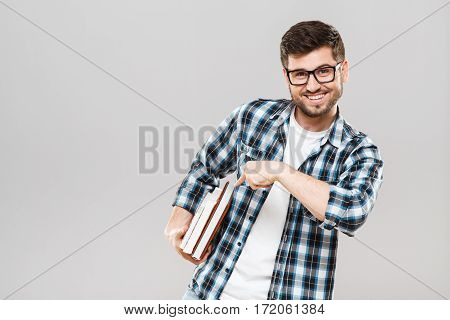 Man in checked T-shirt and eyeglasses looking at camera and smiling. Pointing at books. Holding books. Student, studying, books. Indoors, studio, waist up