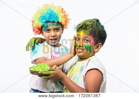 indian kids or boys playing with colours or asian children celebrating holi with pichkari - festival of colours