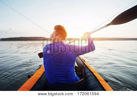 man floating on lake in a kayak at fantastic sunset