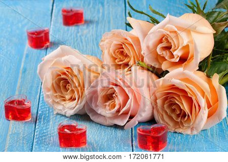 five beige rose with candles in the shape of heart on a blue wooden background.