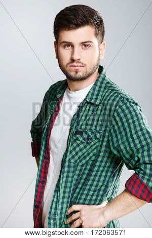 Man in green checked T-shirt half turned aside, looking at camera. Young man, casual style. Half turn, waist up. Hands on waist. Indoors, studio