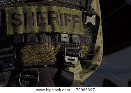 Sheriff patch on tactical vest with plastic buckles